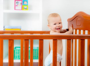 a baby laughs while standing in a crib