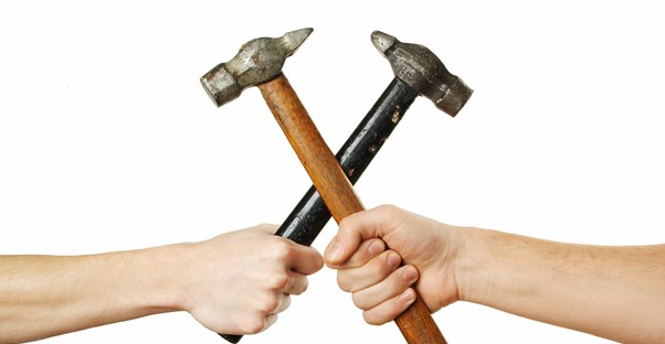 two people holding crossed hammers