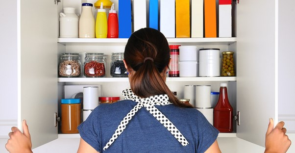a woman gazes into her immaculately organized kitchen pantry