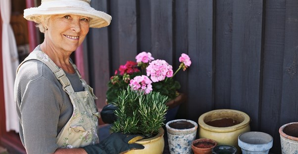 a woman enjoys planting plants in pots for her cost-effective garden