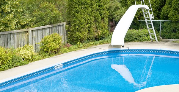 a backyard pool with a slide that may not be worth the investment