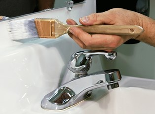 a paintbrush being used to paint a wall above a sink and below a bathroom mirror