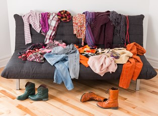 a futon is covered in spare clothing articles