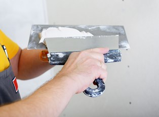 A homeowner prepares to lay tile for his bathroom remodel.