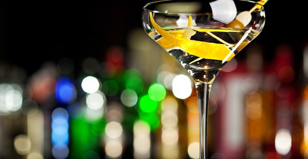 a potent cocktail sparkles in the light of the bar