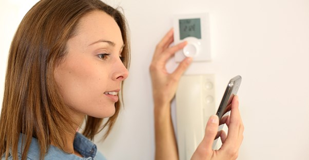 A woman adjusts her home automation system to keep her home safe.
