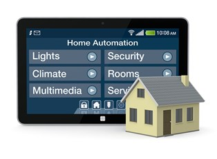A home automation application pulled up on a tablet next to a toy house.