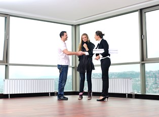 Real estate agent closes a deal with a young couple purchasing a home