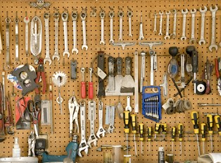 Tools hung on an inexpensive storage rack in a garage