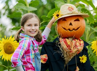 Little girl poses next to a scarecrow in her yard