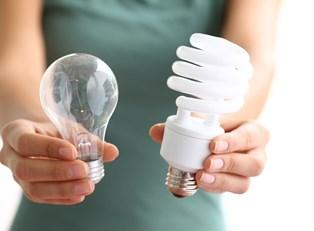 Woman holding out an energy efficient light bulb next to a regular light bulb.
