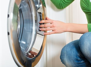 Woman cleaning a washing machine
