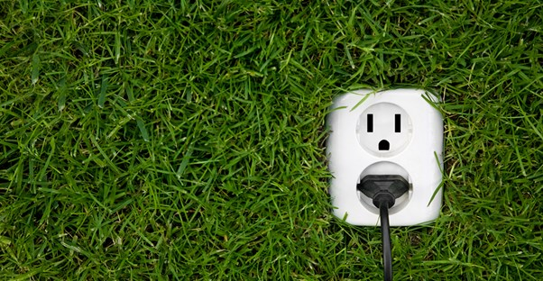 A power plug in the grass to represent energy efficiency