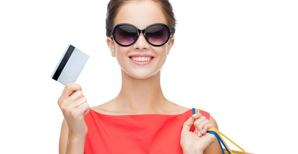 Woman smiling as she uses her credit card to holiday shop