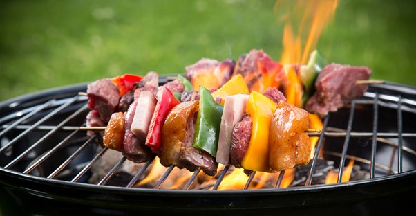 A group of skewers cooking on a grill