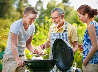 A father discuss the pros and cons of charcoal and gas grills with his hungry children