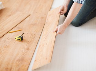 A woman installing a new floor to invest in her home