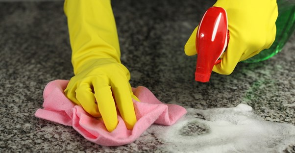 Woman cleaning her granite countertops