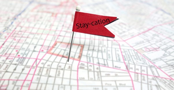 A flag pinned to someones hometown saying staycation