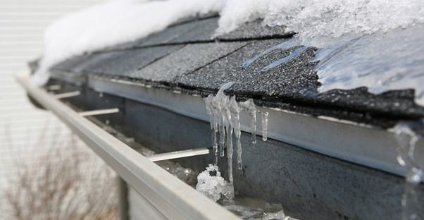 A close up of a shingled roof covered in snow and ice