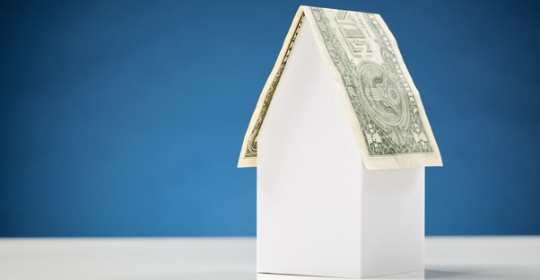 A paper house with a roof made out of money to symbolize that roofing can cost you.