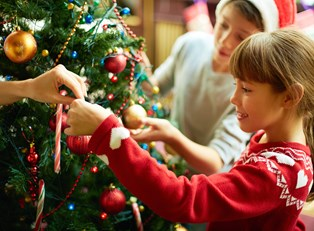 Siblings decorating the family christmas tree