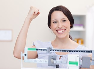 Woman celebrates after her weight loss plan begins to pay off