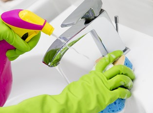 Woman cleaning a sink with a DIY cleaner.