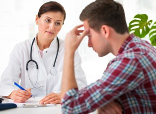 Man discussing how diet can improve his migraine pain with a doctor.