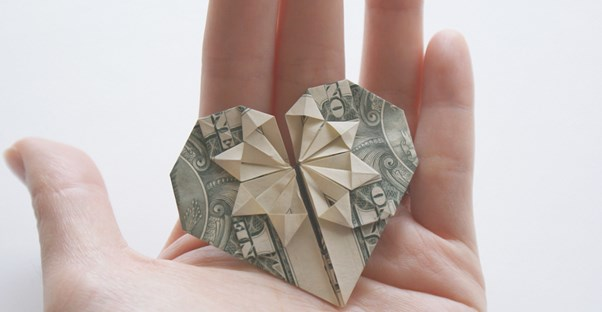 Money folded into a heart to represent donating to charity.