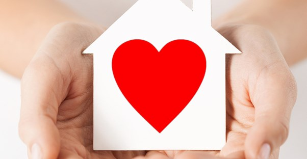Hands holding a paper house with a heart in it to represent that donating is good for you.