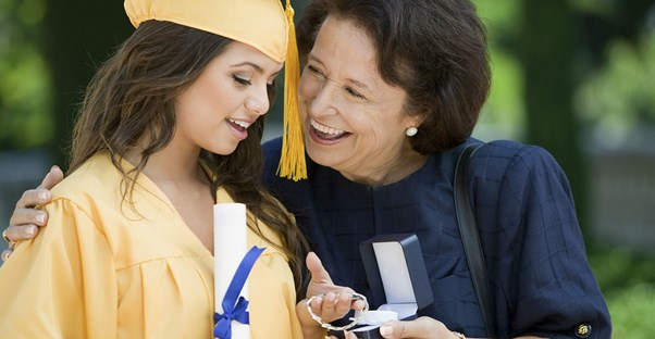 A high school graduate opening a present from her grandmother.