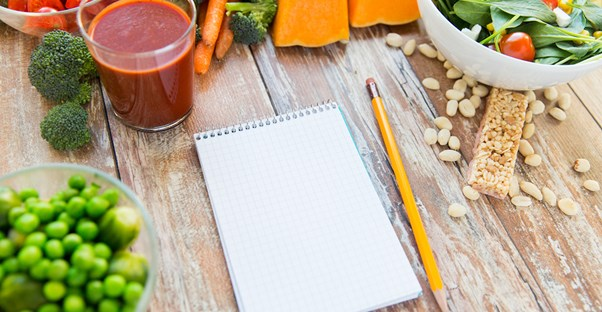 A note pad surrounded by foods for vegan and vegetarian diets