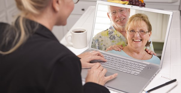 Woman chatting online with older couple