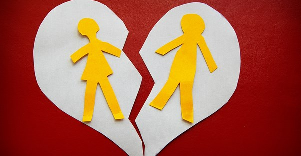 a paper heart with outlines of a man and woman being separated down the middle by a tear