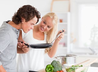 a young couple cooks together and tastes their masterful cuisine