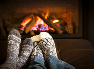 A couple warming their feet by a fire during their romantic staycation