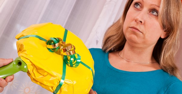 A woman unhappily receiving a skillet from her husband for Christmas.