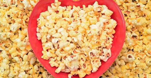 A heart-shaped bowl filled with popcorn to eat on Valentine's Day