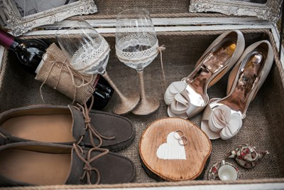 Shoes and wine glasses are laid out as decor for a wedding